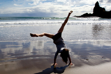 News of a warm summer was enough to make Scarlet Grace, 6, do cartwheels on Piha beach yesterday. Photo / Sarah Ivey