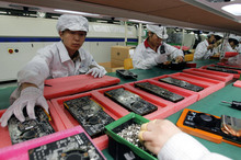 Staff members work on the production line at the Foxconn complex in the southern Chinese city of Shenzhen. Photo / AP