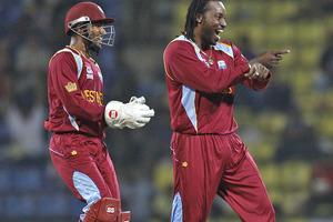 West Indies' wicketkeeper Denesh Ramdin, left, laughs as teammate Chris Gayle dances after he took the wicket of England's batsman Jonny Bairstow. Photo / AP
