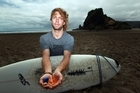 Surfer Chris Cochrane with rubbish found on Piha Beach. Photo / Herald on Sunday