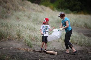 Felix Thompson and Helen Mawn clean up Piha last week. Photo / Sylvie Whinray