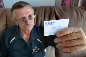 Ross Mulholland can now hold a business card in his damaged hand. Photo / Steven McNicholl