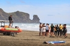Police and lifesavers at Bethells Beach. Photo / Greg Bowker