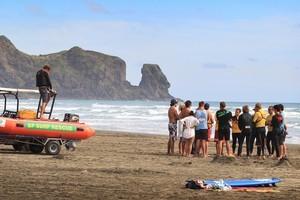 Police and lifesavers at Bethells Beach. Photo / Greg Bowker