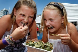 Gracie Bush (left), 12, and Felicity Rood, 10, taste some sea escargots at the Auckland Seafood Festival. Photo / Sarah Ivey