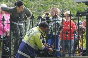 Firefighters work to free Saxon Parry (7) after he jammed his knee in the railing of an iron fence in the Octagon, in Dunedin, yesterday afternoon. His mother, Natalie Parry, left, encourages him. Photo / Craig Baxter.