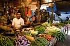 A vendor sells fruit and vegetables at his market stand Photo / Babiche Martens