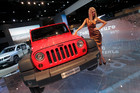 A hostess poses next to a Jeep Wrangler on display at the Paris Auto Show. Photo / AP