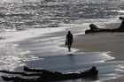 A lone figure enjoys a stroll along the beach between North Mole and Castlecliff in Wanganui. Photo / Bevan Conley