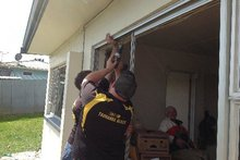 Repair work is carried out after windows of a Tauranga house were damaged by an exploding fridge. Photo / Bay of Plenty Times