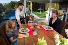 Personal chef Andrei Kainer serves dinner to Hannah Bell (left), 8, Sydney Bell, 5, and Robin Bell. Picture / Sarah Ivey