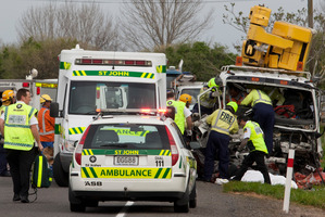 Emergency services help a man trapped in a truck after a head-on near Paengaroa. The car driver died. Photo / Joel Ford