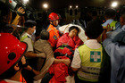A survivor carried by rescuers, is taken onto shore after a collision involving two vessels in Hong Kong. The death toll is now at 25. Photo / AP