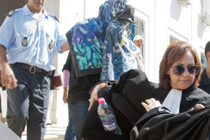 Accused of immoral behaviour, an unidentified Tunisian woman, second right, her face hidden by a black veil, is led by her lawyer, Saida Garrach, as they leave the central Tunis courthouse. Photo / AP