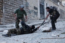Free Syrian Army soldiers help a severely wounded colleague after being shot by a Syrian srmy sniper in Izaa district, earlier this month. Photo / AP
