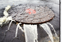 Auckland's trial by rain stressed manholes in Milford. Photo / NZ Herald