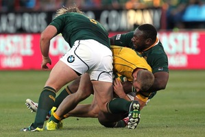 Australia's Dominic Shipperley is tackled by South Africa's Tendai Mtawarira, right, and teammate Jannie du Plessis.  Photo / AP