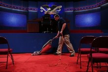 Shaun Spink vacuums during preparation for the Presidential Debate at the University of Denver this afternoon. Photo / AFP