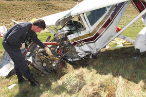 Civil Aviation Authority safety investigator Colin Grounsell examines the wreckage of the Cessna that crashed on the Arrowtown golf course just under a year ago. Photo / James Beech