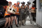 Tui girls Kalinda and Alice deliver refreshments to workers from Geovert Ltd and Higgins Contractors - Lachie Avery, Dan Cochrane, Andy Barlow and Fraser Harvey who helped re-open the Manawatu Gorge. Photo / Mike Watkins
