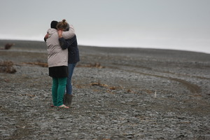 Friends of Victor Boraman comfort each other at the Rakaia River where he disappeared. Photo / Ashburton Guardian