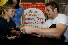 A smile and a chat as Richie McCaw signs his new book, The Open Side, for aspiring All Black Matthew Greenough, 8, in Auckland yesterday. Photo / Sarah Ivey