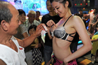 A dancer receives a tip during a temple festival in northern Taoyuan county. She had been hired to appease the wandering spirits. Photo / AFP