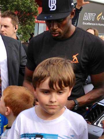 Usain Bolt signs fans' autographs.