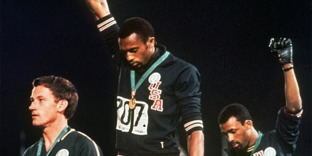 Peter Norman, left, stands during the US national anthem as American sprinters Tommie Smith and John Carlos extend their gloved hands skyward in racial protest. Photo / AP