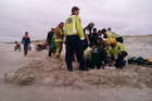 The injured teenager being attended to by St John paramedics inside a sand wall that volunteer firefighters erected at Ruakaka Beach. Photo / Mark Going
