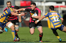 Ryan Crotty of Canterbury breaks through tackles during the