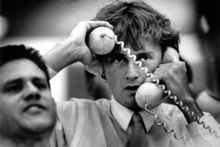 A sharemarket dealer has his hands full during hectic trading at the Auckland exchange in 1987. Photo / APN