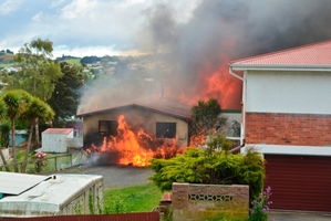 Smoke billows over Green Island from two house fires yesterday. Photo / Daniel Olsen