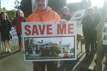 About a dozen people waved placards outside the villa in Herne Bay. Photo / Bernard Orsman