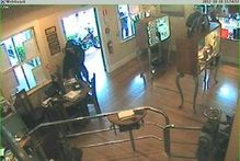 A thief can be seen reaching inside the store and taking the charity box. Photo / Supplied