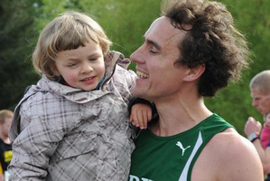 Dougal Thorburn carries his daughter, Audrey, after setting a world record for the fastest 10km run while pushing a pram. Photo / Otago Daily Times