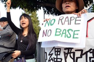 Civic group members shout slogans and hold placards as they attend a protest over the alleged rape of a local woman by two US servicemen in Okinawa. Photo / AFP