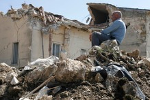 A man sits on rubble in the village of Onna, a day after a powerful earthquak
