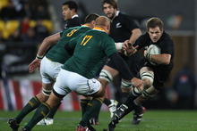 Richie McCaw of the All Blacks fends off CJ Van Der Linde of the Springboks during the Tri-Nations match. Photo / Getty Images
