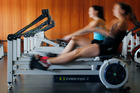Lucy Spoors (foreground) and Kelsey Bevan work out on the erg machines at Lake Karapiro. Photo / Christine Cornege