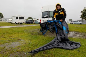 Brian Riley from Warkworth packs up his drenched tent to move to a cabin at the Kopua Holiday Park at Raglan. Photo / Christine Cornege