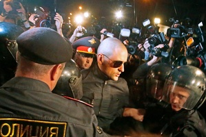 Police officers detain opposition leader Sergei Udaltsov, in sunglasses, after a protest rally in Moscow, Russia. Photo / AP