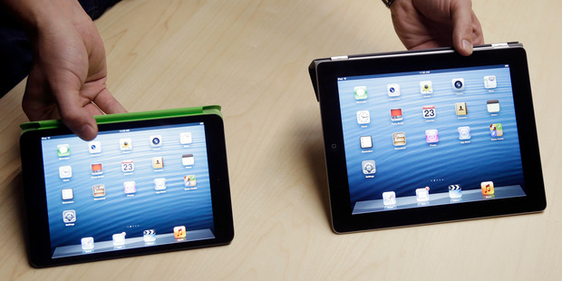 The iPad Mini, at left, is shown next to the 4th Generation iPad. Photo / AP
