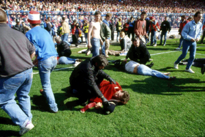 April 15, 1989 file photo, showing police, stewards and supporters as they tend to wounded soccer supporters on the field at Hillsborough Stadium, in Sheffield, England. Photo / AP
