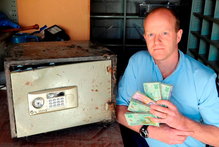 Sergeant Craig Dinnissen with the money and the safe found in the bush. The safe is believed to have been from a burglary two years ago. Photo / Linda Robertson