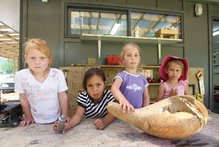Amber Gleeson, Nevaeh-Lee Matiu,3, Isabella Troughton,4, and Sangreal Ekins, 3, of Maungaarangi Kindergarten with a gourd that was smashed by vandals. Photo / Joel Ford