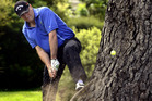 John Key hits out of a tricky lie during a charity golf match in Dunedin yesterday. Photo / ODT