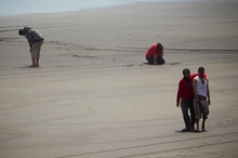 Members of the drowned man's family on Muriwai Beach. Photo / Dean Purcell