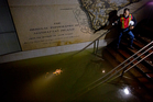 Joseph Leader, Metropolitan Tranportation Authority Vice President and Chief Maintenance Officer, shines a flashlight on standing water inside the South Ferry 1 train station in New York. Photo / AP