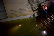 Joseph Leader, Metropolitan Tranportation Authority Vice President and Chief Maintenance Officer, shines a flashlight on standing water inside the South Ferry 1 train station in New